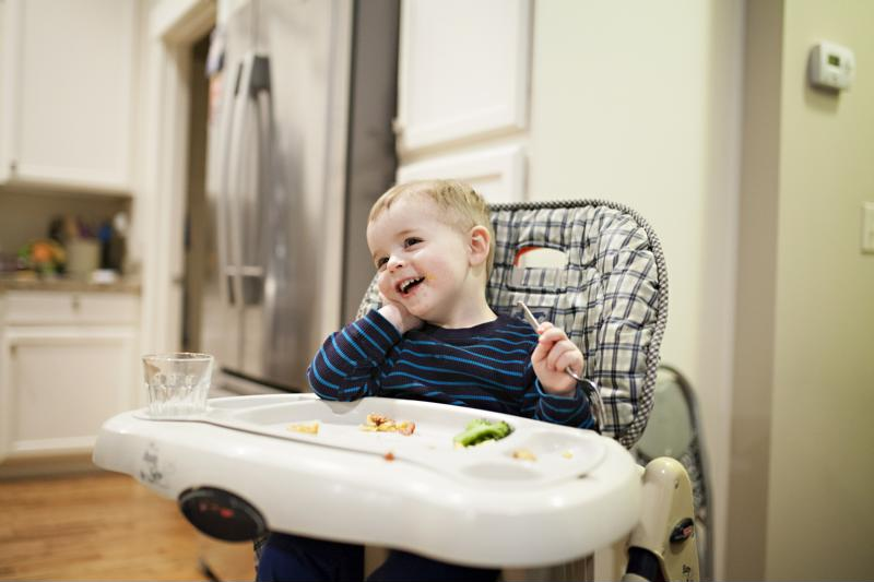 A smiling toddler eating dinner in a high chair.