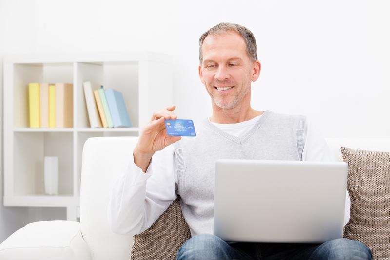 A customer holds up a credit card while shopping online.