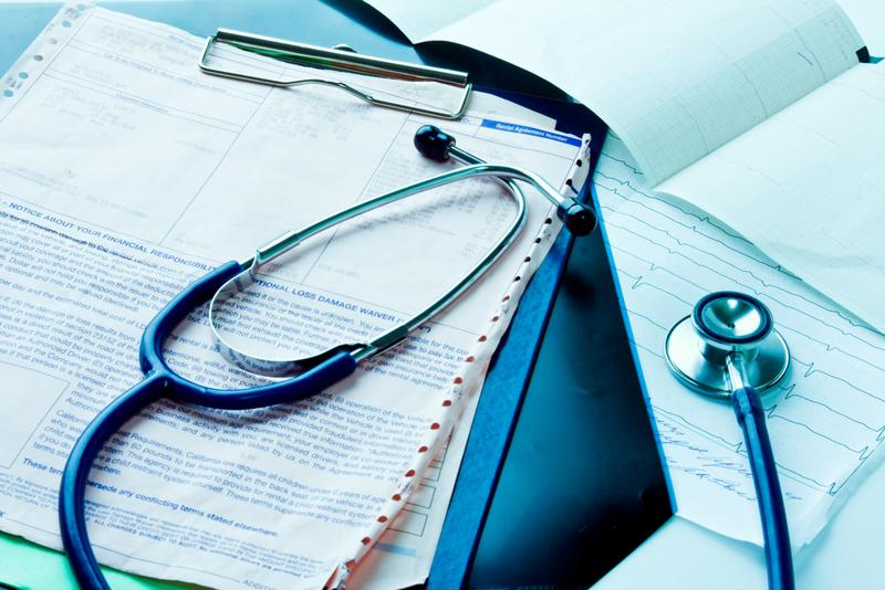Medical records and stethoscope on desk.