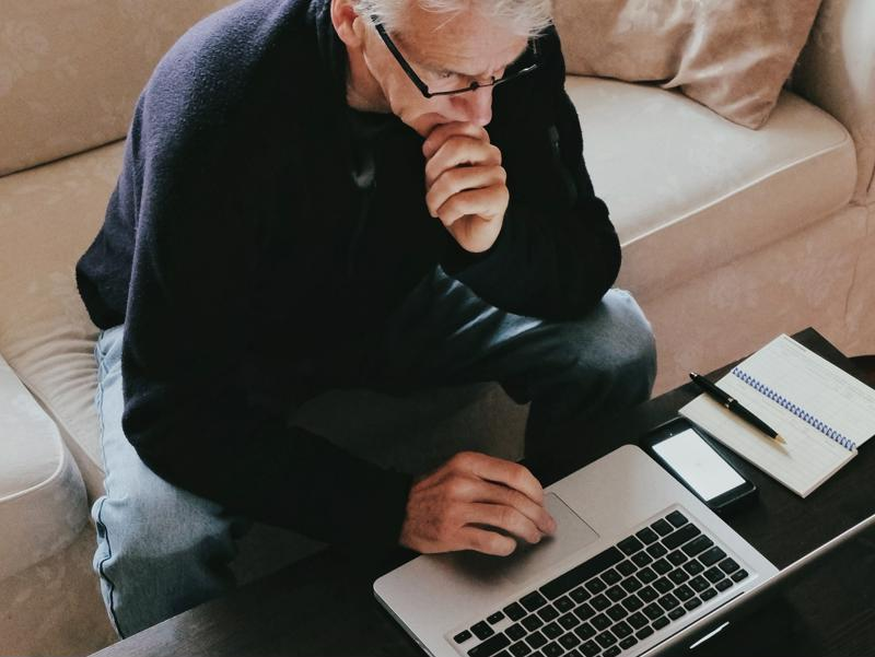 White-haired man working from home, sitting on couch with laptop & devices on coffee table