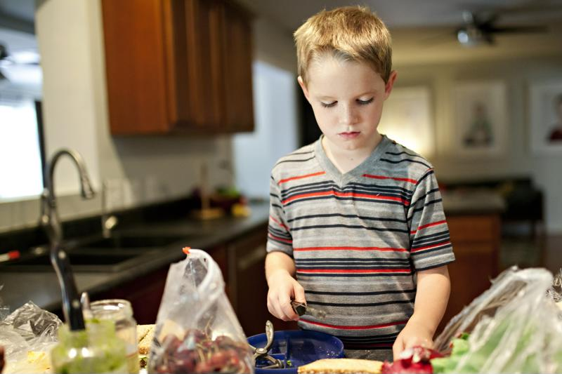 A young boy preparing his lunch in a kitchen.