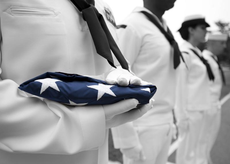 Service members holding a folded flag.