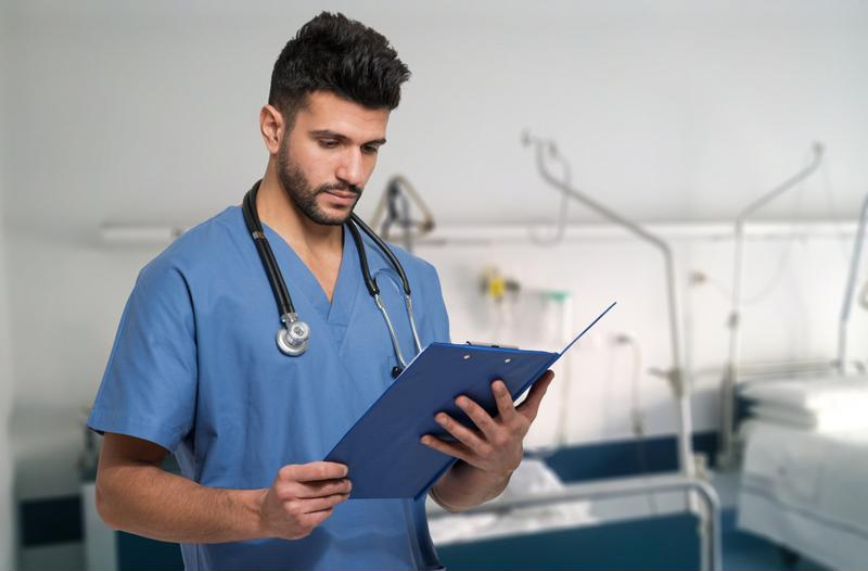 Male nurse holding a chart in the hospital.