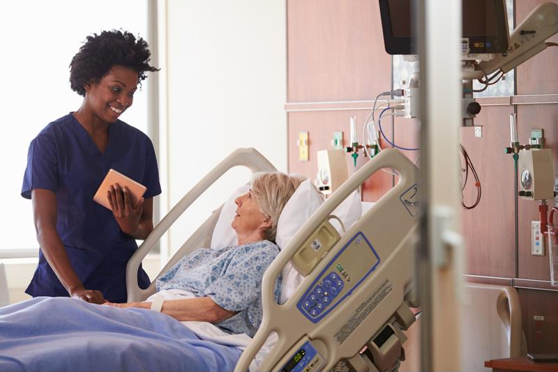 African American nurse wearing blue scrubs standing at the bedside of an elderly, female patient in a hospital room.