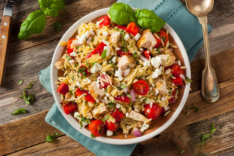 Bowl of chicken orzo salad with peppers and feta on a wood table.