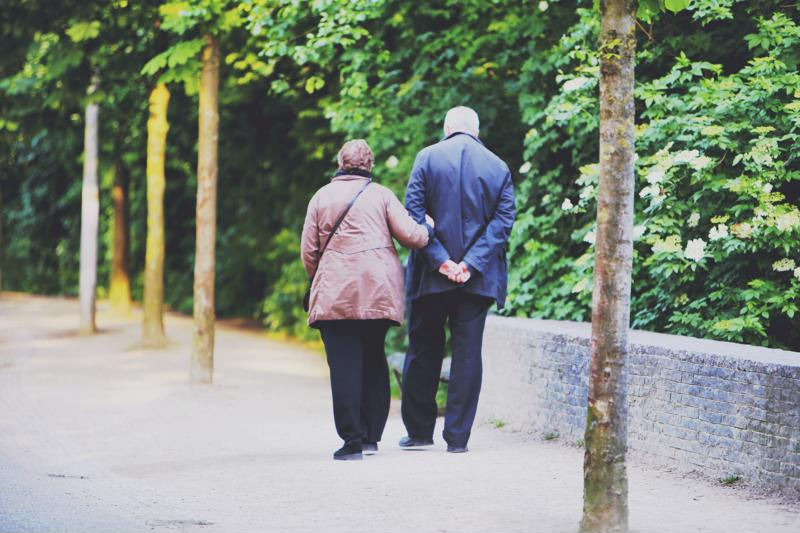 Older couple walking together arm in arm.