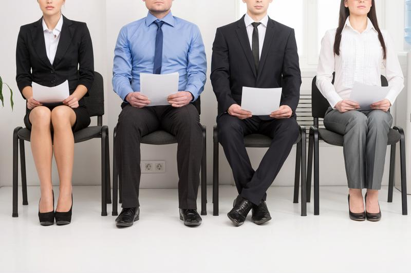Job candidates hold their resumes.