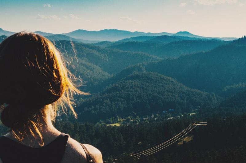 A woman overlooks forests and mountains.