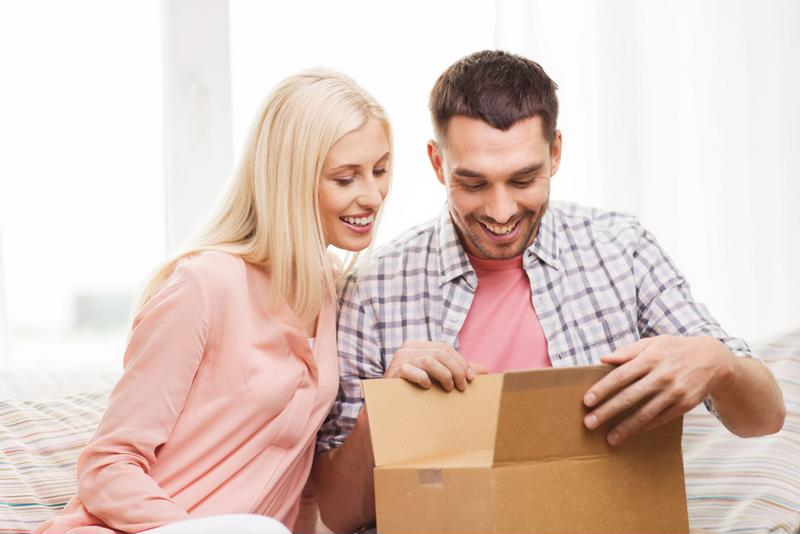 Man and woman opening a box with smiles on their faces.