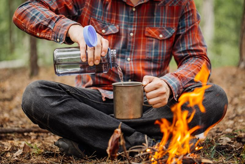 A camper pours water into a tin cup.