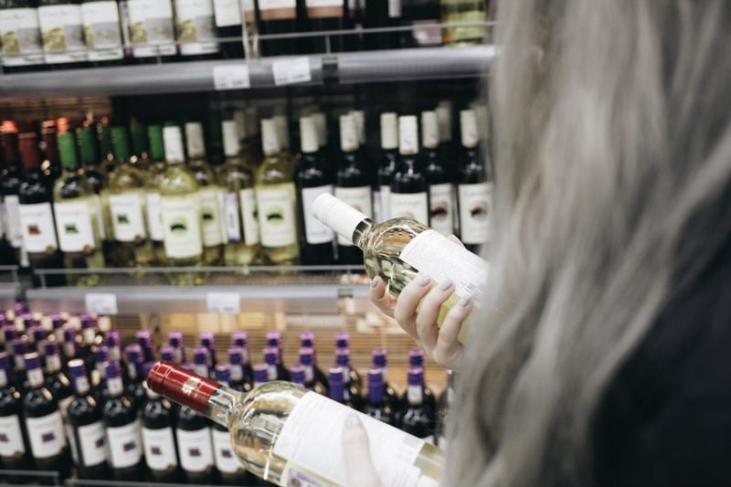 Woman choosing between two bottles of wine at the store.