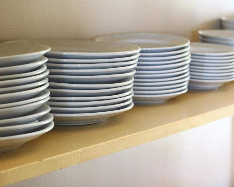 Open shelves filled with stacked white plates.