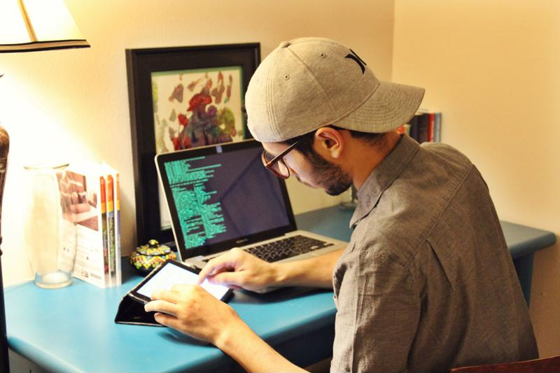 Man using tablet and laptop to code