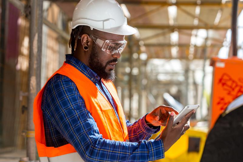 man in construction gear checking documents on tablet