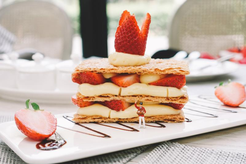Mille-feuille with strawberries and chocolate drizzle on white plate.