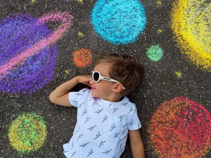For an out-of-this-world photograph, use sidewalk chalk to draw our solar system.
