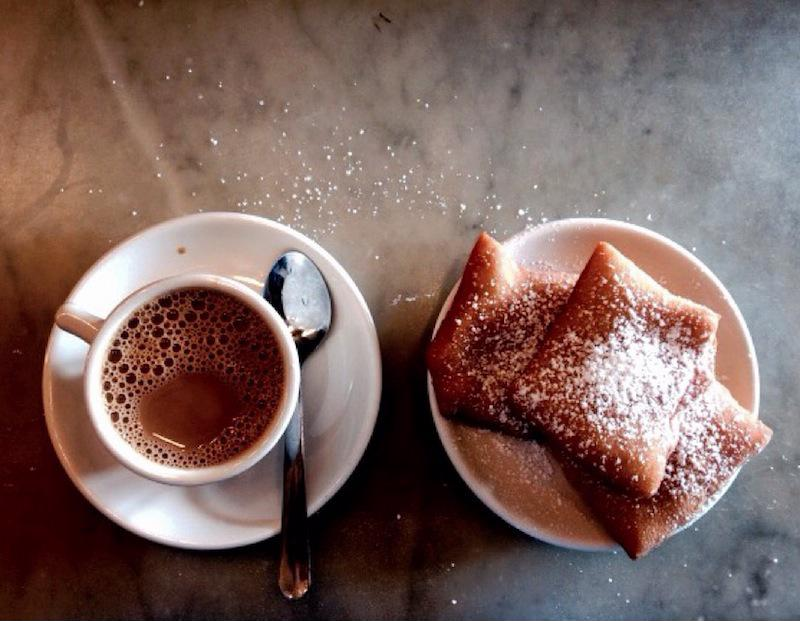 Two beignets topped with powdered sugar rest next to an espresso.