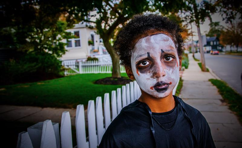 boy with Halloween face makeup on stares into the camera