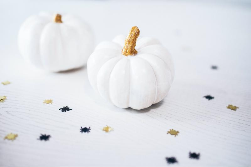 Two white pumpkins with spider glitter around them.