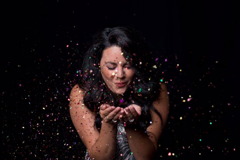 Woman blowing a handful of confetti into the air.