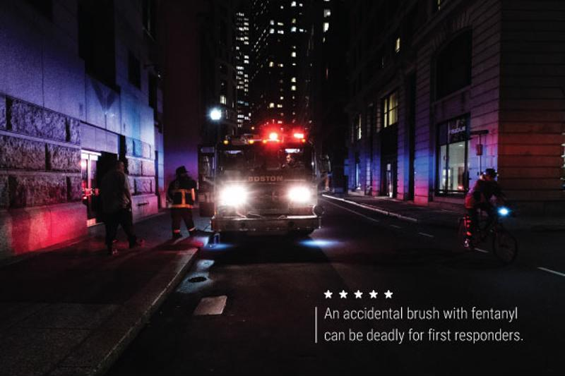 """A night shot of a firetruck and firefighters. Text reads, """"An accidental brush with fentanyl can be deadly for first responders."""""""