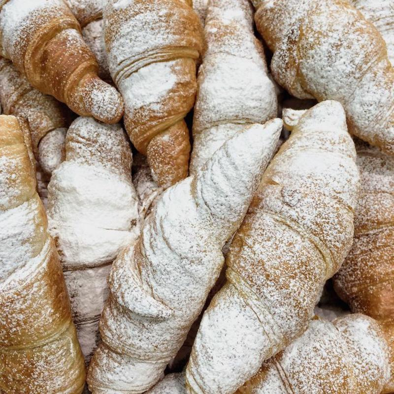 A bowl of croissants dusted with powdered sugar.