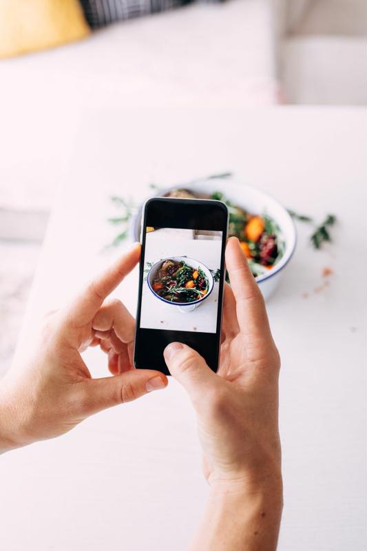 A chef takes a picture of a plated dish with a smartphone.