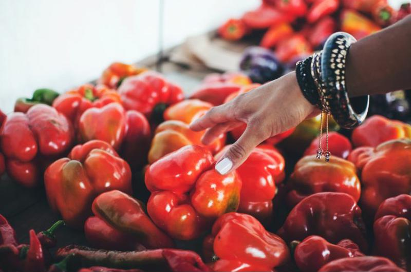 A hand reaches for a red bell pepper from a stand.