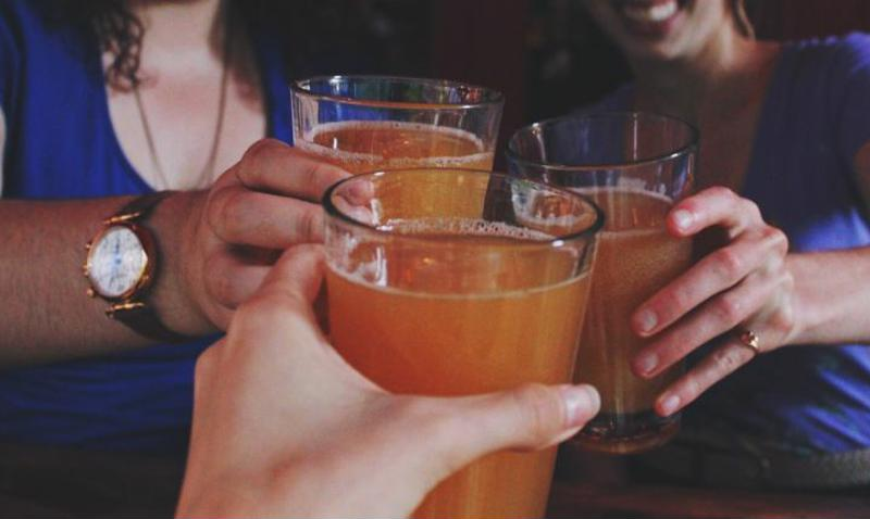 Closeup of three people holding glasses of cider.