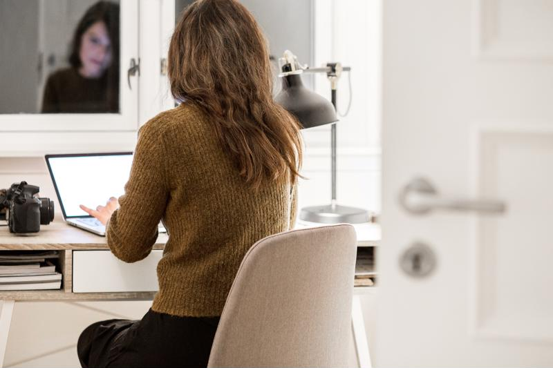 A woman works at a laptop at home.