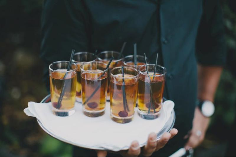 Plate of drinks held by waiter.