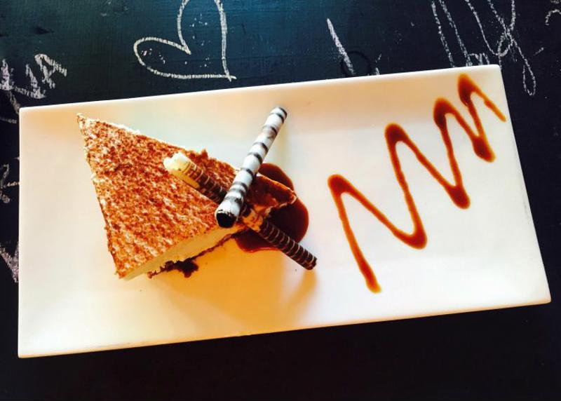 A chocolate pastry is carefully plated, complemented by shaved chocolate and a chocolate drizzle.