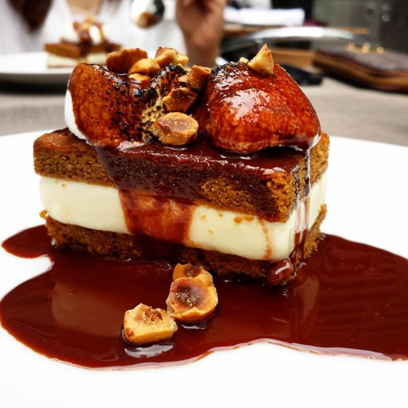 An ice cream sandwich topped with chocolate, hazelnuts and marshmallows sits on a white china plate.