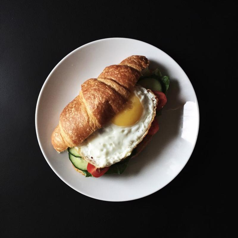 A croissant topped with a fried egg