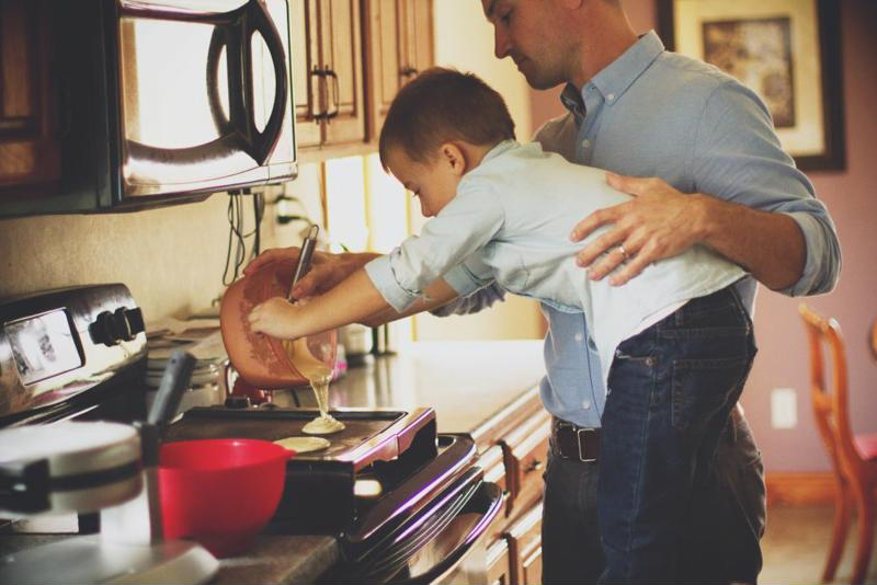 A father helping a child make pancakes.