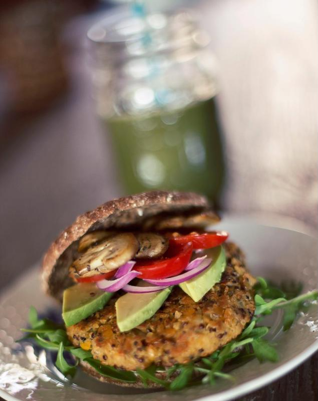 A burger topped with avocado, onion, mushrooms and bell pepper is served on a plate.