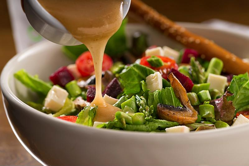 Vinaigrette being poured onto a salad
