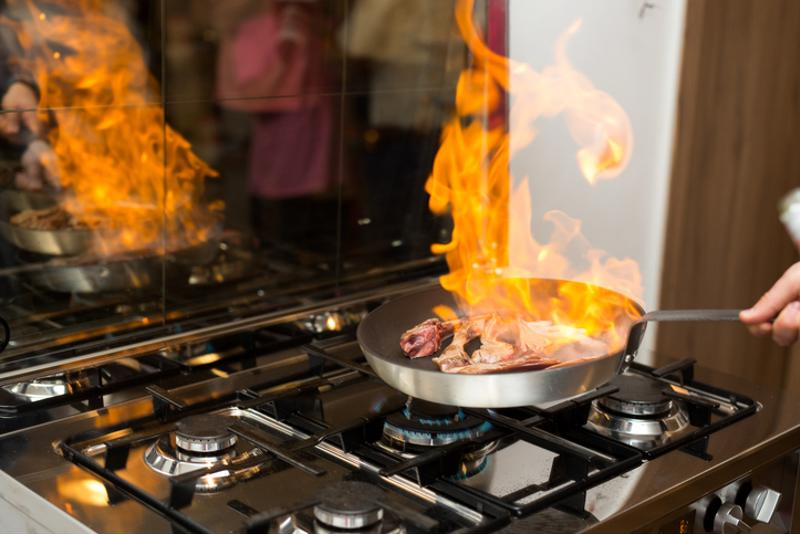 A chef flambing meat in a pan on a stove