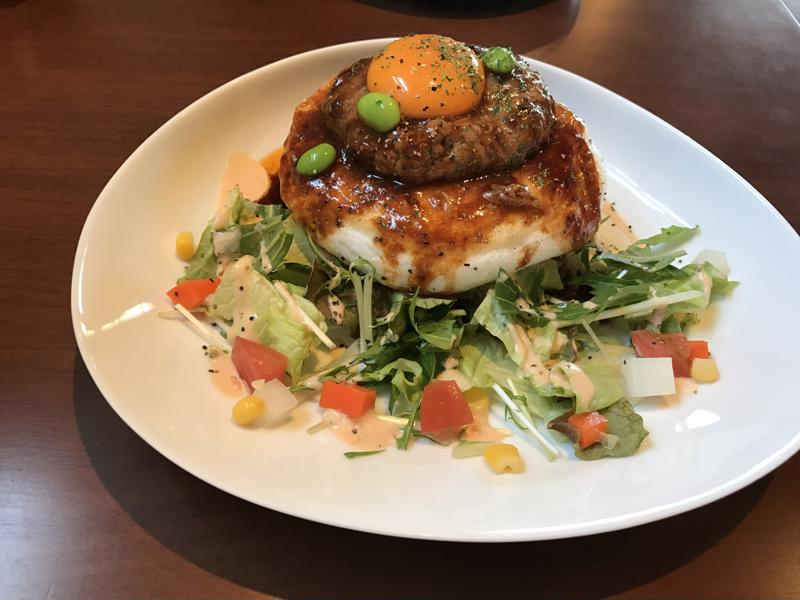 A close up shot of a plate holding a loco moco and salad.