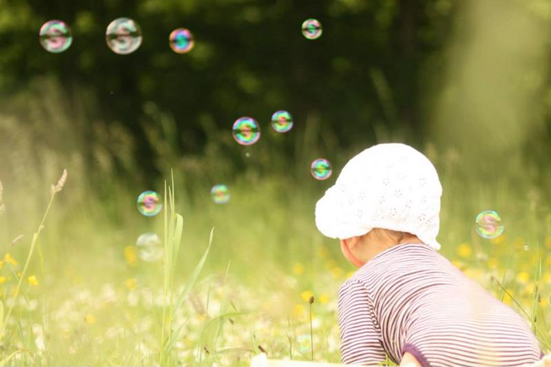 A baby chases after bubbles.