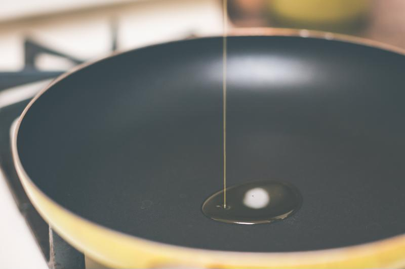 Oil drizzled into a cooking pan.