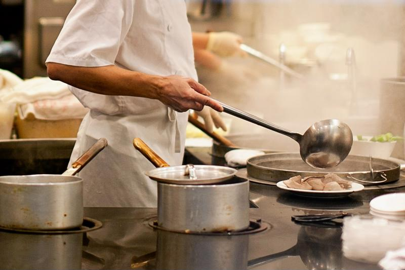 A chef working in a busy, steamy kitchen.