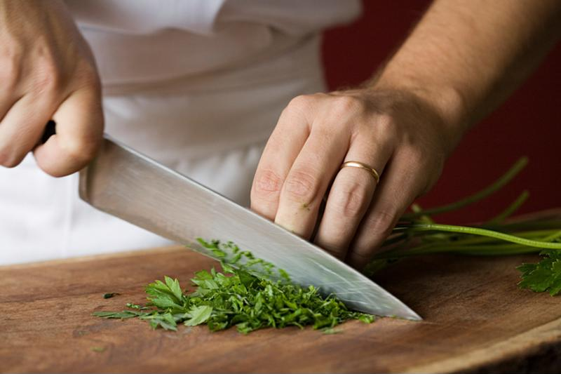 Hand with a knife chopping herbs