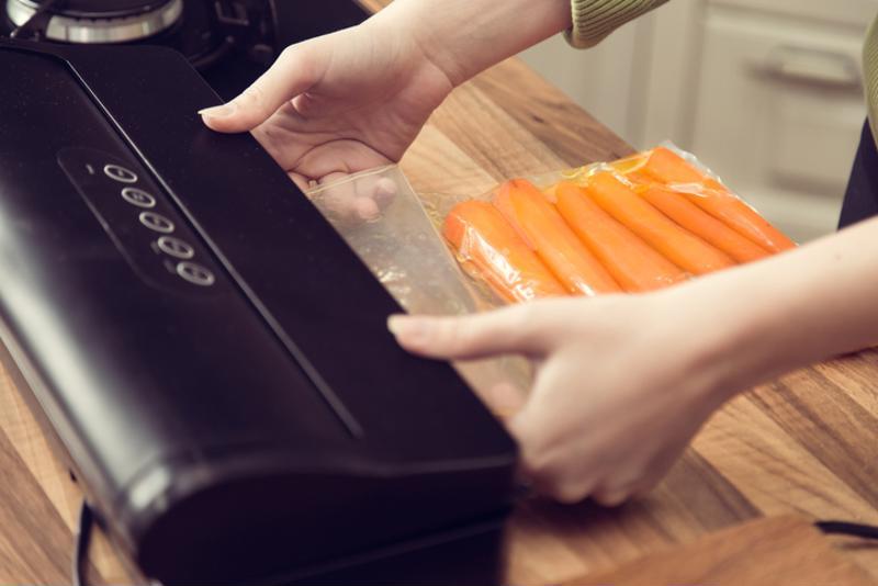 A woman vacuum seals carrots