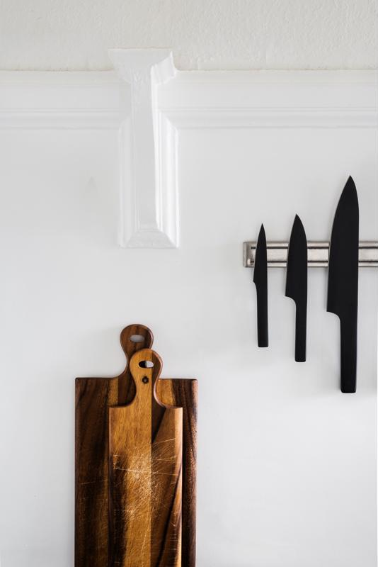 Chefs knives and wooden cutting boards are displayed in an all-white kitchen.
