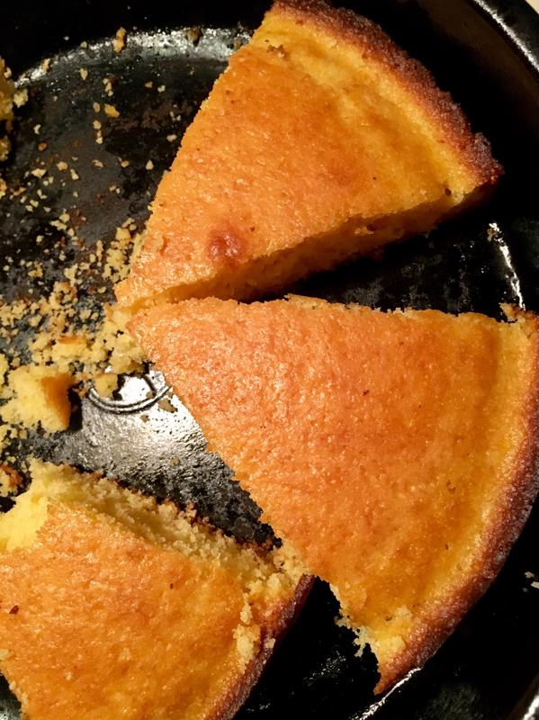 A skillet with wedges of cornbread inside.