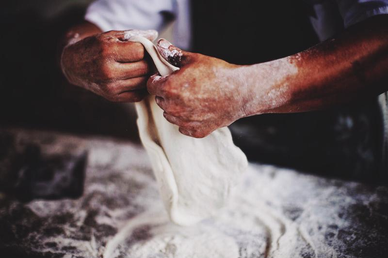 Close up shot of a chef kneading dough.