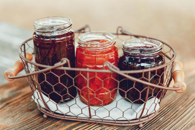 Berry jams in jars in a basket
