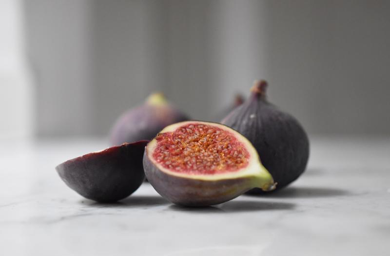 A close up of a halved fig with more figs in the background.