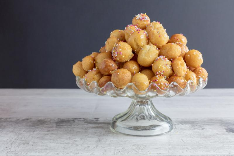 Struffoli with sprinkles in a glass dish.